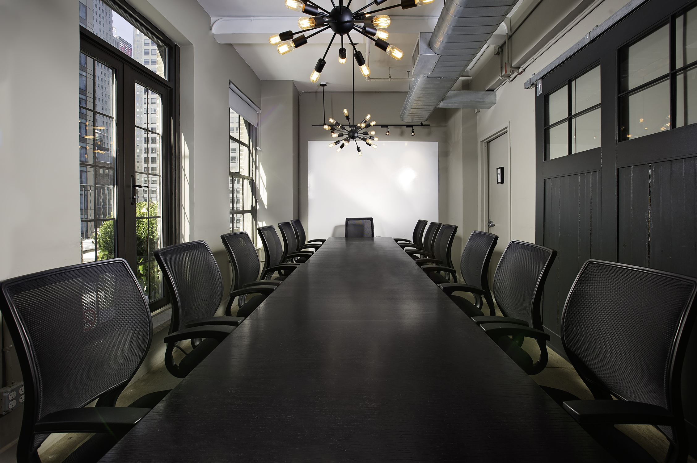 Large black conference room table adjacent to outdoor terrace space