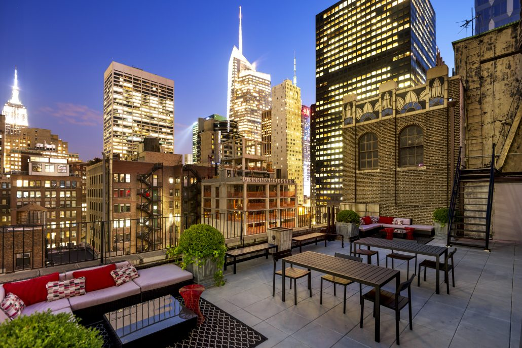 Nighttime view of outdoor terrace with illuminated Empire State building in background